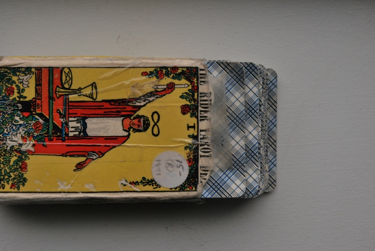 Close up of Rider Waite Tarot Deck with the blue plaid back of the cards peeking out of worn, and taped box.