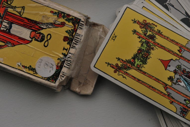 a close up of a Rider Waite Tarot Deck that displaces the 4 of Wands card face up.